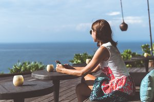 Woman sitting in a tropical restaurant with ocean view. Original place. Space for text. Bali island.
