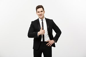 Business Concept: Portrait of excited man with opened mouth dressed in formal wear giving thumbs-up against gray background.