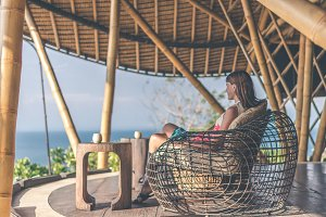 Woman sitting in bamboo restaurant. Original place. Space for text. Bali island.