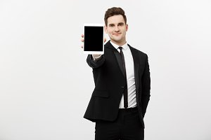 Business Concept: Smiling handsome businessman presenting website or presentation on tablet.