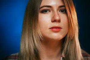portrait smiling girl on blue background in studio