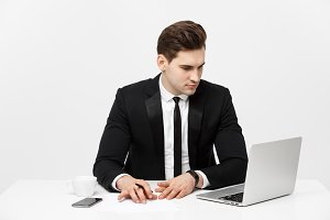Portrait of a handsome businessman holding smartphone while working on a computer at his desk. He is in a office his notebook in front of him like an insurance or bank manager.