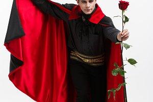 Vampire Halloween Concept - Portrait of handsome caucasian Vampire holding red beautiful rose.