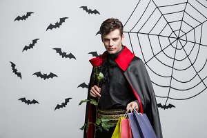 Vampire Halloween Concept - Happy handsome caucasian Vampire holding colorful shopping bag.