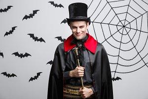 Vampire Halloween Concept - Portrait of handsome caucasian Vampire in black and red halloween costume singing with staff.