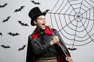 Vampire Halloween Concept - Portrait of handsome caucasian Vampire in black and red halloween costume singing with staff.