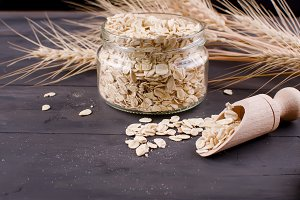 Oat flakes in jar, spoon and spikele