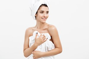 Beauty and Skin care concept - Beautiful caucasian Young Woman with bath towel on head covering her breasts, on white