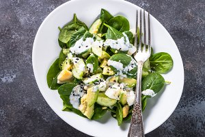 Green salad with avocado, spinach egg and cucumber.