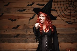 Halloween witch concept - Happy Halloween red hair Witch holding posing with magic wand over old wooden studio background.