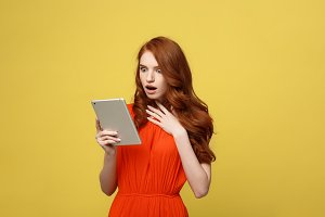 Technology and Lifestyle Concept: Surprised young woman wearing orange dress clothes using tablet pc isolated on vivid yellow background