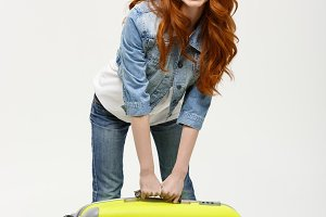 Travel and Lifestyle Concept: Young woman suffers from back pain lifting a heavy suitcase isolated on yellow background