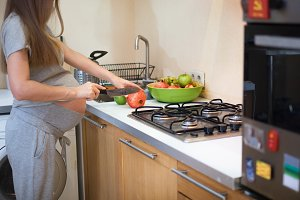 Pregnant woman cutting healthy food in kitchen for eating - vegetables and fruits