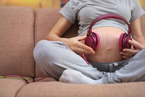 Pregnant woman sitting on a couch and holding headphones on belly. Unborn child listens to music with headphones.