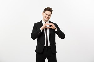 Business Concept: Portrait of charming attractive businessman holding hands in heart gesture and lifting eyebrows while smiling, isolated over white grey background.
