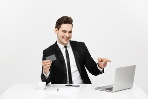 Modern technology, business, career, e-commerce and online trading concept: Caucasian businessman holding credit card in one had and pointing on laptop with other hand.