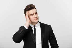 Business Concept: Young businessman with holding hands on head with headache facial expression isolated over white background