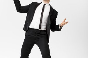 Business Concept - Handsome cheerful businessman showing hands in air over gray background.