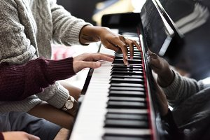 Couple practicing on a piano