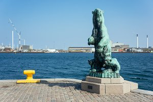 Polar bear with cubes bronze statue in the port of Copenhagen near deep blue sea at sunny day, industrial landscape of Denmark. The statue was made by Holger Wederkinch.