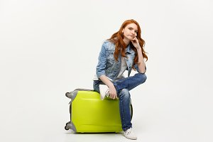 Travel and Lifestyle Concept - Portrait young red hair woman sitting on a bag with boring facial expression, isolated on bright yellow background.