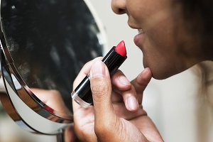 Woman putting on lipstick at mirror