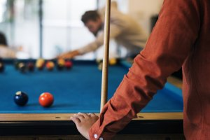 Happy friends playing pool together