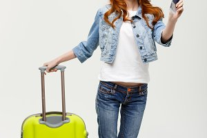 Travel and Lifestyle: Portrait of an excited young caucasian woman dressed in summer clothes holding passport with flying tickets while standing with a suitcase isolated over bright yellow background