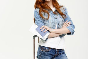 Portrait of trendy young ginger girl standing with suitcase and holding passport with tickets, over white or grey background