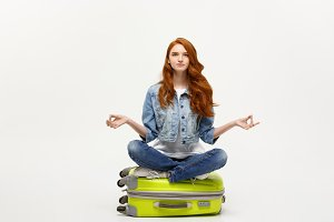 Traveling concept. Young pretty ginger woman meditating in lotus pose on the luggage valise. Isolated on white.