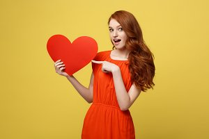 Valentine and Lifestyle Concept: Portrait of an attractive young woman dressed in red dress pointing finger at paper heart isolated over yellow studio background.