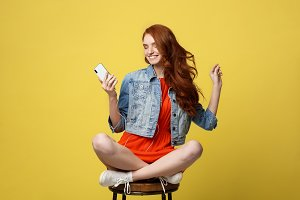 Lifestyle, Music, Technology concept: Young beautiful caucasian woman listening music with headphones and smart phone hand hold, dancing, eyes closed smiling, Isolated on yellow vivid background.