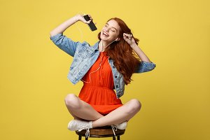 Lifestyle Concept - Happy pretty red hair woman in earphones listening to music and singing while sitting on chair and holding mobile phone. Isolated on bright yellow background