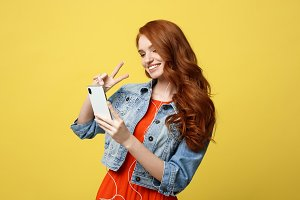 Lifestyle Concept - Portrait ginger hair woman in casual dress using mobile phone for interaction video calling by showing two fingers. Isolated on bright yellow background