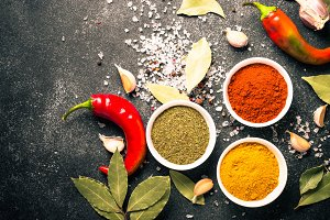 Various spices in a bowls on stone table.