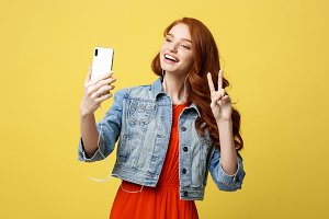 Lifestyle Concept: Young cheerful woman posing while photographing herself on smart phone camera for a chat with her friends, attractive smiling hipster girl making self portrait on cell telephone.