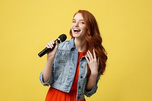 Lifestyle and People Concept: Expressive beauty ginger hair model girl in casual jean cloth singer with a microphone.