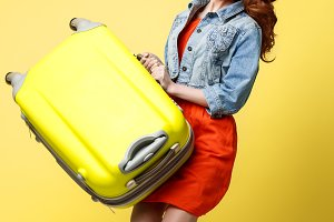 Travel and Lifestyle Concept: Portrait of a beautiful red hair fashion woman jumping and holding a bright green suitcase isolated over bright yellow background.