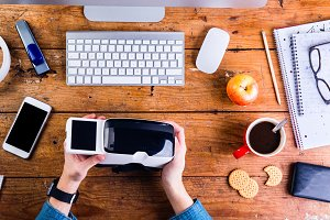 Businessman working at office desk holding virtual reality goggl