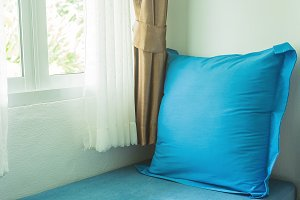 blue pillow near in glass window