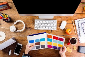 Designer at office desk working with color swatches