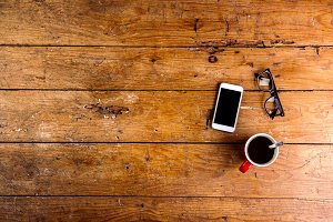 Smartphone, cup of coffee and eyeglasses on office desk