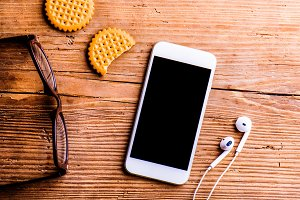 Smartphone, earphones, eyeglasses and other objects on office de