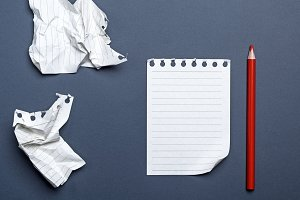 notepad and red wooden pencil