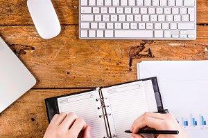 Businessman writing into personal organizer, wearing smart watch