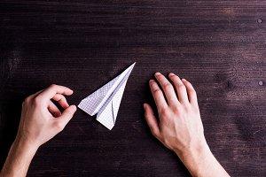 Hands of man, paper plane. Wooden background. Studio shot.