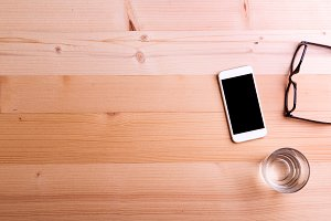 Smartphone, glass of water and eyeglasses on office desk