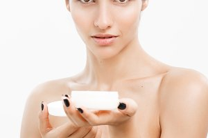 Beauty Youth Skin Care Concept - Close up Beautiful Caucasian Woman Face Portrait presenting cream jar for skin care over white background.