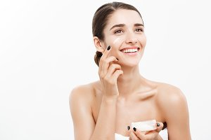 Beauty Youth Skin Care Concept - Close up Beautiful Caucasian Woman Face Portrait applying some cream to her face. Beautiful Spa model Girl with Perfect Fresh Clean Skin over white background.
