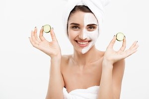 Beauty Youth Skin Care Concept - Portrait Beautiful Caucasian Woman apply cream and holding fresh cucumber in front of her face.Isolated over white background.